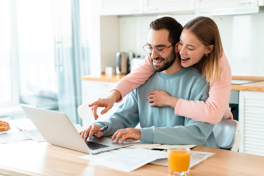 Portrait of smiling couple hugging while working with laptop
