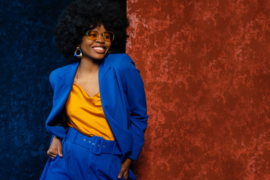 African American fashionable woman wearing yellow sunglasses, top, classic blue suit. Young beautiful happy smiling model posing near colorful walls. Fashion portrait. Copy, empty space for text