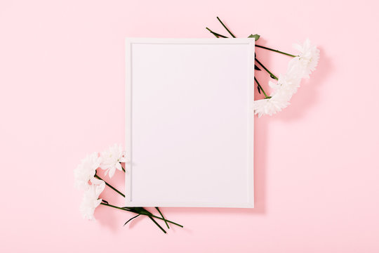 Beautiful flowers composition. White photo frame, white flowers on pastel pink background. Valentines Day, Happy Women's Day, Mother's day. Flat lay, top view, copy space