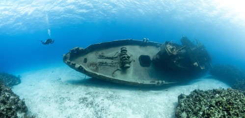 Scuba divers examining the famous USS Kittiwake submarine wreck in the Grand Cayman Islands