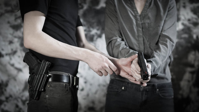 Woman receiving one-on-one firearms training from instructor. Concealed carry, and personal defense concept.