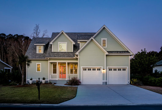 Front elevation of beautiful home lit up at twilight.