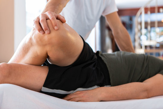 A sportsman receiving medical massage of legs. A young man lying on the massage table and having a treating leg massage in the medical center