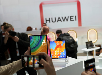 People take pictures of Huawei Mate Xs foldable smartphone and a Huawei MatePad Pro during Huawei product launch event in Barcelona