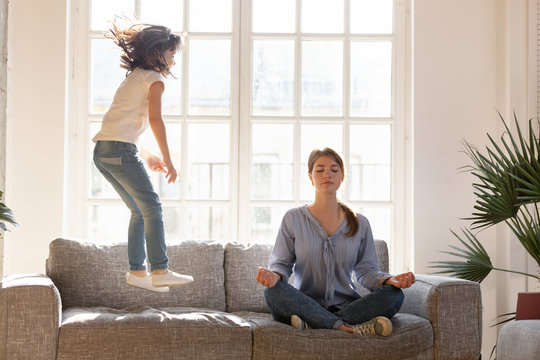Mom meditating on couch ignore kid jumping near
