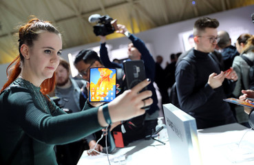 Woman takes a selfie as she holds a Huawei Mate Xs foldable smartphone during Huawei product launch event in Barcelona