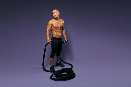 handsome man with perfect body and slim waste holding ropes and looking at the camera. full length photo, isolated blue background, studio shot, copy space, free time, spare time