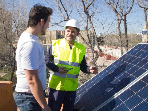 Caucasian seasoned technician talking to his young client beside the solar panels