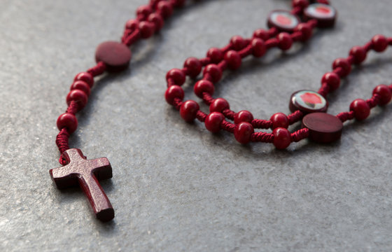 Red rosary on a stone background
