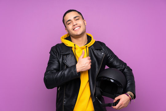 Man with a motorcycle helmet isolated on purple background giving a thumbs up gesture
