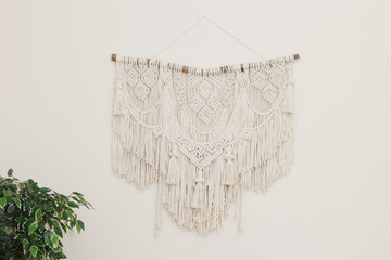.Macrame wall panel made of natural cotton threads on a light wall. for home decor in the style of Boho..