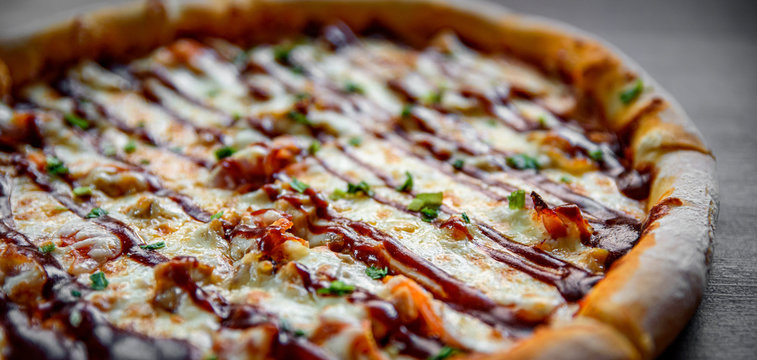 Pizza with chicken and barbeque sauce . Italian pizza on wooden table background