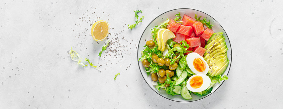 Ketogenic, keto or paleo diet lunch bowl with salted salmon fish, lemon, avocado, olives, boiled egg, cucumber, green lettuce salad and chia seeds. Healthy food trend. Top view. Banner