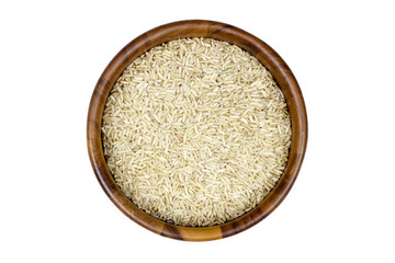 Uncooked brown rice in a wooden bowl on white background