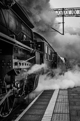Old vintage train locomotive making steam starting from railway station