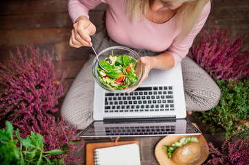 Top view of senior woman with laptop sitting outdoors on terrace,eating lunch. Fototapete