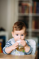 Cute baby boy drinking tea from bottle.