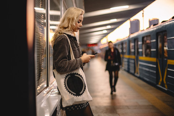 Young woman using smartphone while waiting for subway train on platform