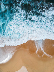 Aerial drone view of beach and ocean waves crashing no people