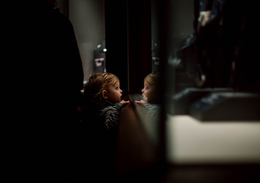 toddler looking through glass at museum exhibits with reflection