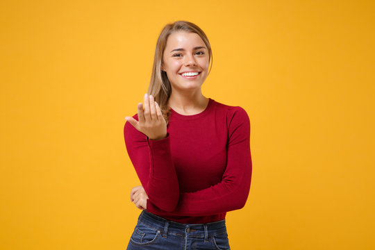 Smiling young blonde woman girl in casual clothes posing isolated on yellow orange background in studio. People lifestyle concept. Mock up copy space. Doing calling gesture like says come here to me.