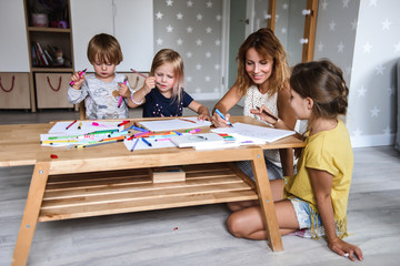Mom with young children drawing with felt-tip pens