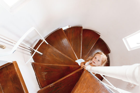 Girl descending the circular stairs in a white dress