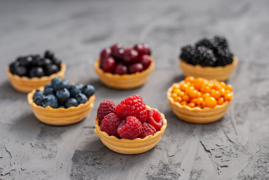 Homemade tartlets from shortcrust pastry with different ripe berries - raspberries, blueberries, blackberries, sea buckthorn, dogwood, chokeberry on a dark background