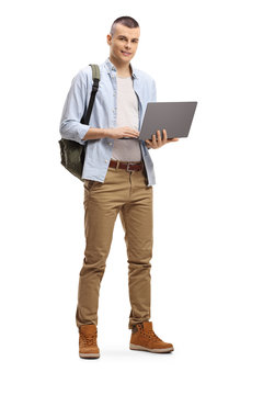 Male student standing and using a laptop computer