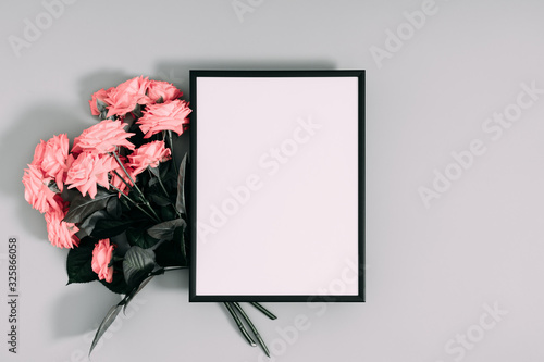 Beautiful flowers composition. Blank frame for text, pink rose flowers on gray background. Valentines Day, Birthday, Happy Women's Day, Mother's day. Flat lay, top view, copy space