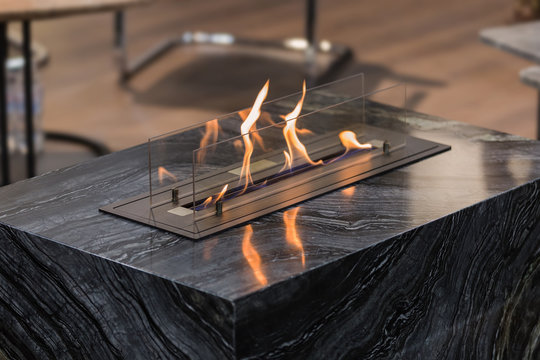 Beautiful marble black floor fireplace. Minimalism interior, alternative bio fireplot fireplace on ethanol gas