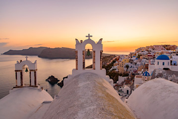 Foto auf Leinwand Santorini Blue domed churches and bell tower facing Aegean Sea with warm sunset light in Oia, Santorini, Greece