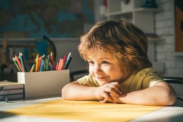 Cute face of pupil, close up. Pupil learning letters and numbers. Children learning. Cute child boy in classroom near blackboard desk.