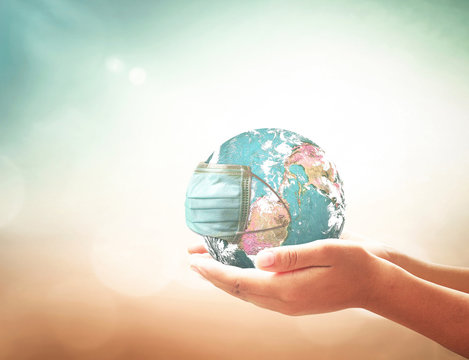 COVID-19 prevention concept: Human hands holding earth globe with medical disposable face mask. Elements of this image furnished by NASA
