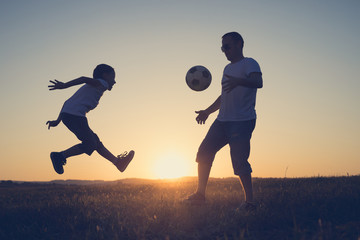 Father and young little boy playing in the field  with soccer ball.