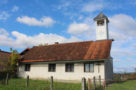 Elongated small old local catholic church with white bell tower covered with metal roof and shiny new cross on top surrounded with uncut grass and cloudy blue sky background