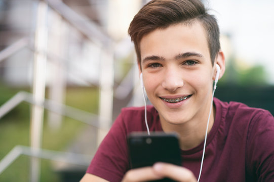 Close-up portrait of a smiling young man with a smartphone, in the street.  Happy teenage boy is using mobile phone, outdoors. Cheerful teenager spends time in social networks using cell phone.