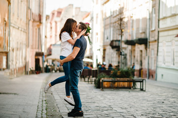 Smiling Young couple with a bouquet of flowers in love hug each other in love outdoors. Love and tenderness, dating, romance. Lifestyle concept. Wall mural