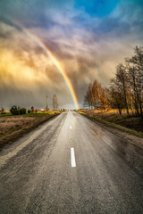 Spoed Fotobehang Grijs Early spring landscape with dramatic sky, rainbow and road lines