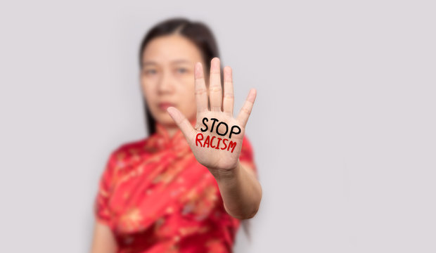 Asian woman in Chinese costume doing stop gesture with palm hand with message stop racism. warning expression with negative and serious gesture.
