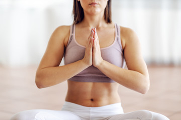 Close up of attractive muscular young brunette sitting in lotus position and meditating.