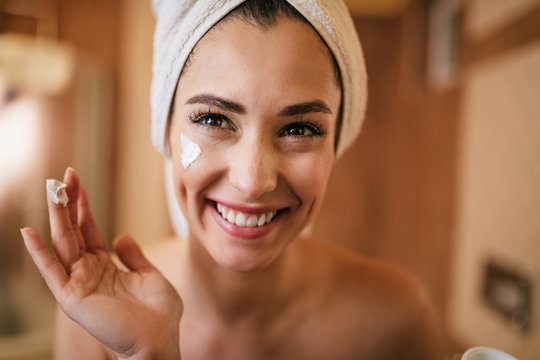 Young happy woman applying moisturizer on her face in the bathroom.