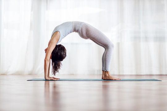 Side view of flexible slim attractive brunette with long hair in Wheel yoga position. Yoga studio interior.