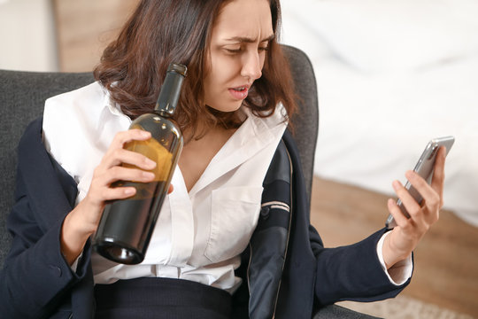 Drunk woman with mobile phone at home. Concept of alcoholism