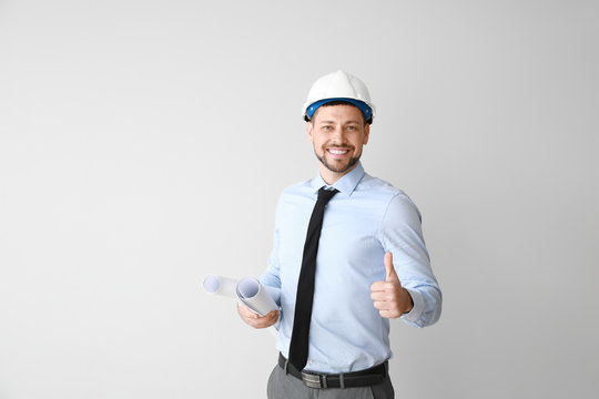Male engineer showing thumb-up gesture on light background