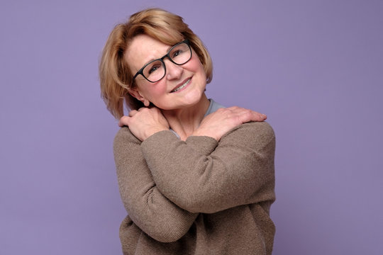 Positive senior caucasian woman in glasses smiling, keeping arms around herself.