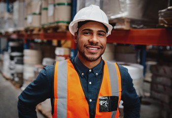 Happy warehouse manager standing in factory wearing white helmet and orange safety vest looking at camera smiling Wall mural