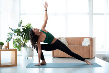 Young Hispanic woman doing yoga at home. Triangle pose Wall mural