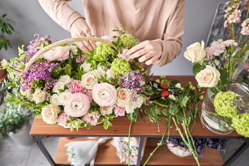 Tuinposter Bloemen Education in the school of floristry. Master class on making bouquets. Summer bouquet in a wicker basket.. Learning flower arranging, making beautiful bouquets with your own hands. Flowers delivery