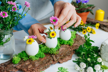 Female hands making Easter decoration with eggs and flowers inside it